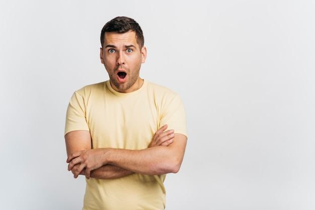 Shocked man with arms crossed and copy space