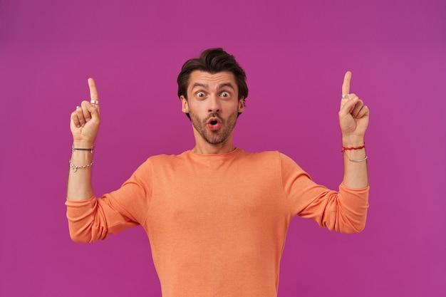 Шокированный мужчина с темными волосами и щетиной. оранжевый свитер с закатанными рукавами. имеет браслеты, кольца