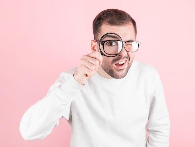 운동복에 재미있는 표정으로 안경을 든 충격을받은 남자는 분홍색 돋보기를 통해 보인다.