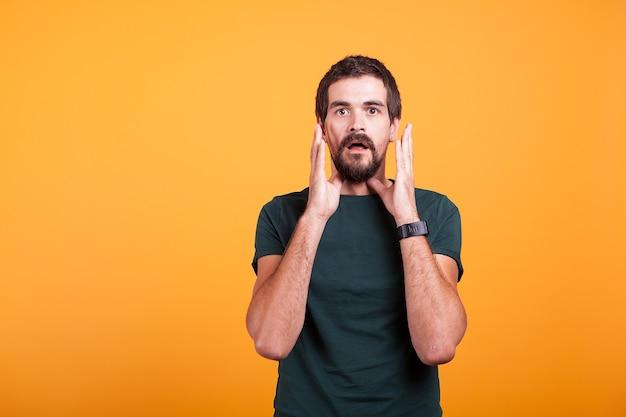 カメラを見て彼の顔に手でショックを受けた男。広告やプロモーションに利用できるコピースペース