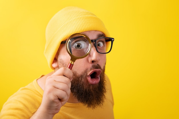 Shocked man with magnifier over yellow background