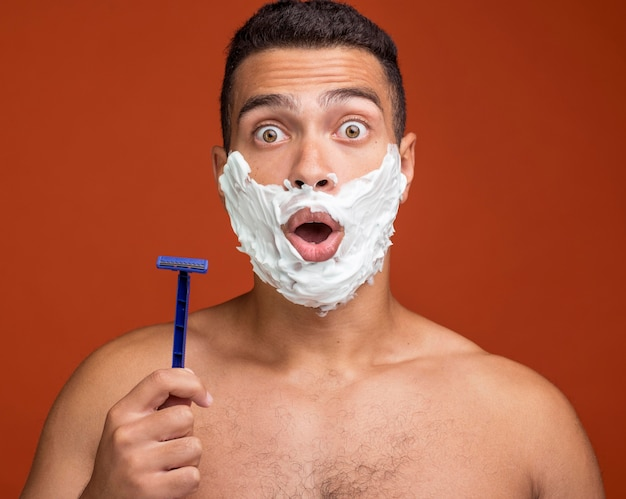 Shocked man with shaving foam on his face holding razor