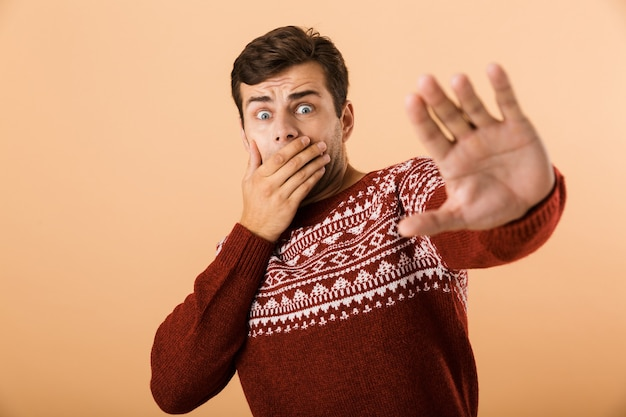 Shocked man with stubble wearing knitted sweater doing stop gesture with hands, isolated over beige wall