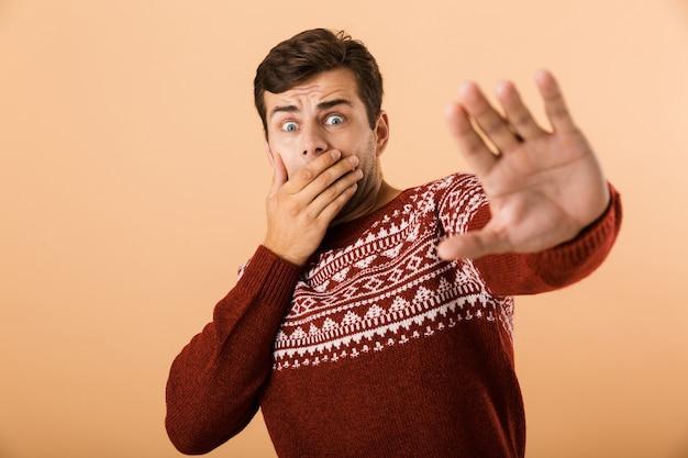 Шокированный мужчина с щетиной в вязаном свитере делает стоп-жест руками, изолированный на бежевой стене