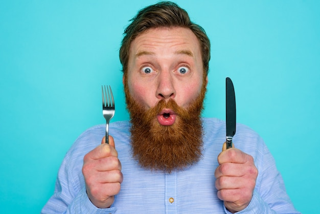 Shocked man with tattoos is ready to eat something with cutlery in hand