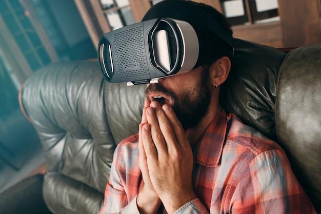 Потрясенный человек в очках виртуальной реальности.
