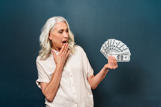 Сотрясенная зрелая старуха показывая деньги держа в руках.