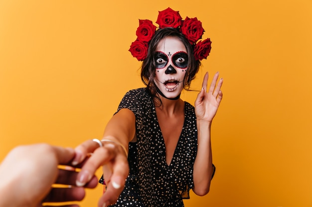 Потрясенный мексиканский зомби смешно позирует на желтом фоне. вдохновленная женщина-модель в костюме на хэллоуин, выражающая изумление.