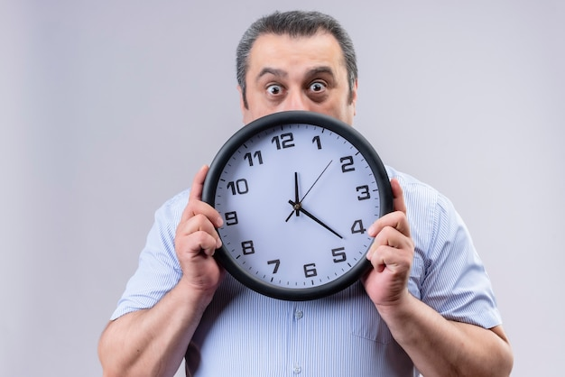 Shocked middle age man in blue striped shirt holding wall clock showing time while standing on a white background