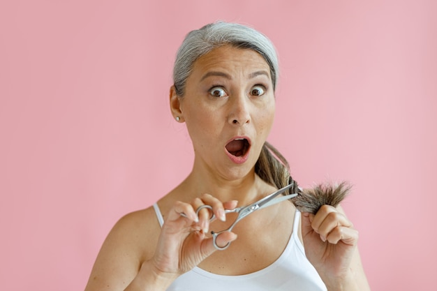 Shocked middle aged asian lady cuts split ends of grey hair on pink background