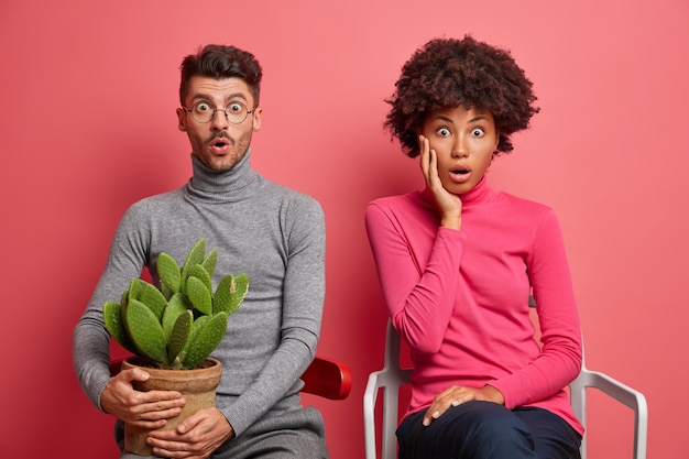 Shocked mixed race young woman and man sit next to each other impressed by shocking news pose on comfortable chairs dressed in casual clothing