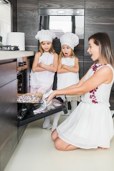 Shocked mother and daughter looking at backed cookies in kitchen