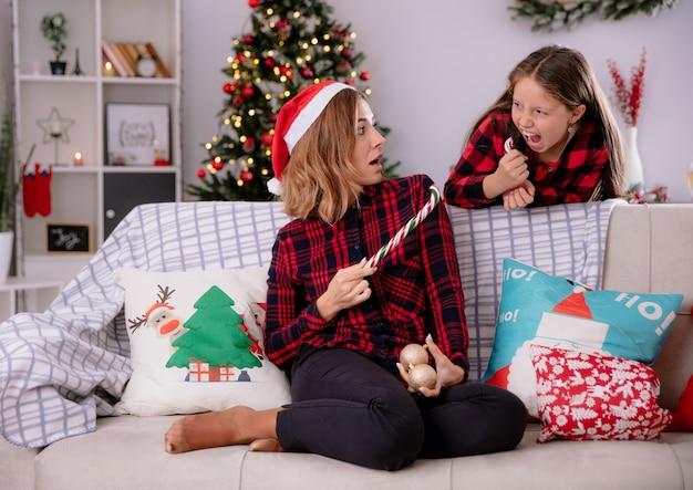 산타 모자와 충격을받은 어머니는 소파에 앉아 깨진 사탕 지팡이의 일부를 보유하고 집에서 사탕 지팡이 크리스마스 시간의 일부를 들고 화가 딸을 찾습니다