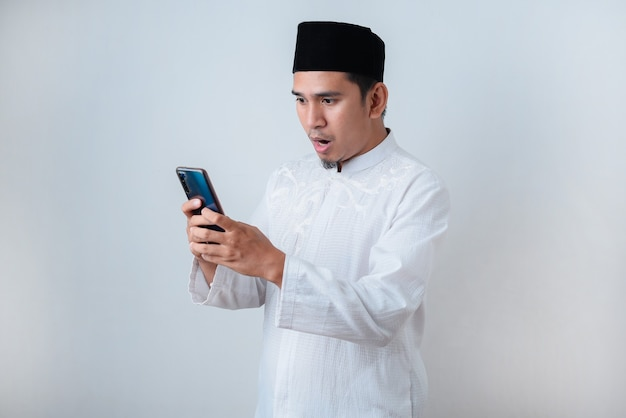 Shocked muslim man wearing muslim clothes holding mobile phone look at phone screen against on white wall