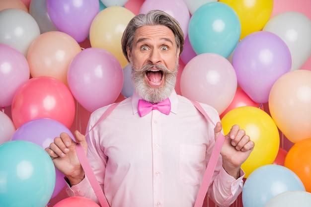 Шокирован старик на фоне воздушного шара, потянув подтяжки