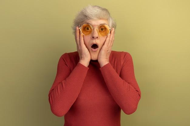 빨간 터틀넥 스웨터와 복사 공간이 올리브 녹색 배경에 고립 된 얼굴에 손을 댔을 카메라를보고 선글라스를 착용 충격 늙은 여자