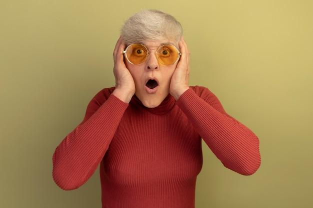 Donna anziana scioccata che indossa un maglione a collo alto rosso e occhiali da sole che mettono le mani sulla testa