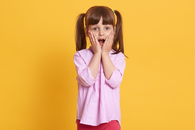 Потрясенная или удивленная красивая милая маленькая девочка закрывает рот руками