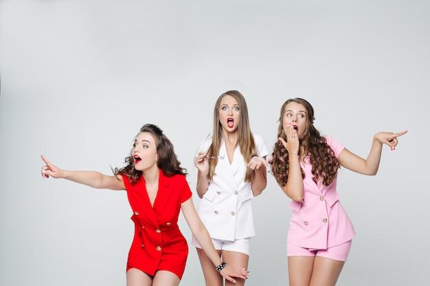 Шокированные или удивленные девушки в костюмах указывают на что-то в воздухе.