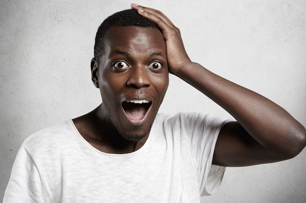 Шокированный или удивленный молодой красивый африканский мужчина, кричащий от ужаса или страха с рукой на голове и широко открытым ртом, боясь опоздать на окончательную продажу. черный мужчина чувствует себя подчеркнутым.