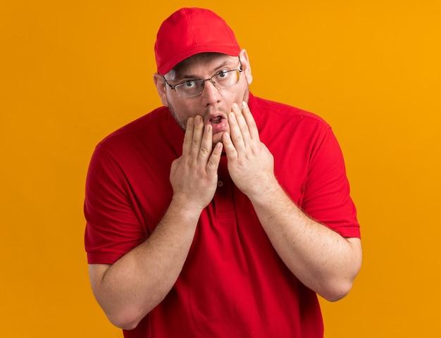 Scioccato sovrappeso giovane fattorino in occhiali ottici mette le mani sul viso isolato sulla parete arancione con copia spazio