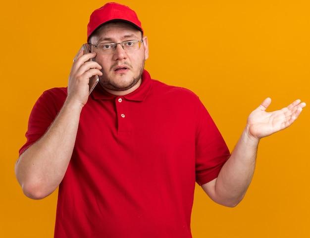 Scioccato sovrappeso giovane fattorino in occhiali ottici parlando al telefono isolato sulla parete arancione con copia spazio