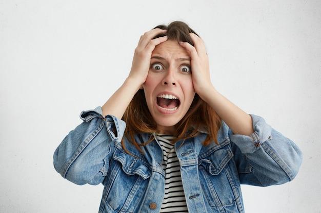 Шокированная паника кавказская девушка, одетая в стильную одежду, держится за руки за голову и кричит от отчаяния и разочарования