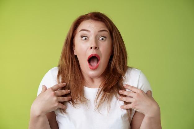 충격을당한 당황한 빨간 머리 중년 여성 헐떡 거리는 드롭 턱 벌리고 입을 쳐다보고 카메라 freakout 불안한 자신을 가리키는 겁에 질린 겁에 질려 초조하게 반응 녹색 벽