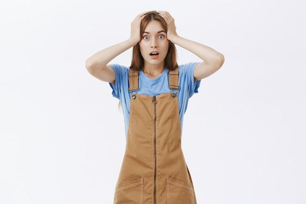 La donna in preda al panico scioccata afferra la testa e sembra ansiosa, ha un grosso problema