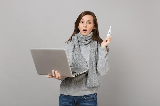 회색 스웨터를 입은 당황한 젊은 여성, 회색 배경에 격리된 온도계를 들고 노트북 컴퓨터에서 작업하는 스카프. 건강한 생활 방식, 온라인 치료 컨설팅, 추운 계절 개념.