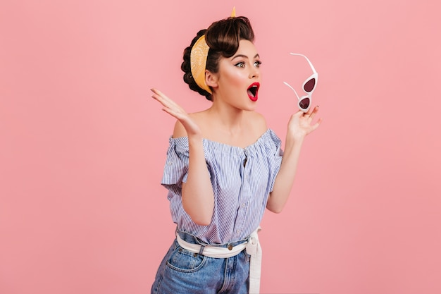 선글라스를 들고 충격 된 핀 업 소녀입니다. 분홍색 배경에 고립 된 빈티지 복장에 감정적 인 여자의 스튜디오 샷.