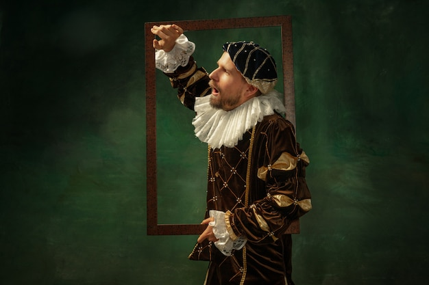 Shocked. portrait of medieval young man in vintage clothing with wooden frame on dark background. male model as a duke, prince, royal person. concept of comparison of eras, modern, fashion, sales.