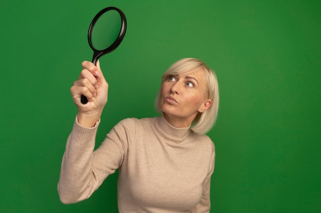 Shocked pretty blonde slavic woman holds and looks at magnifying glass on green