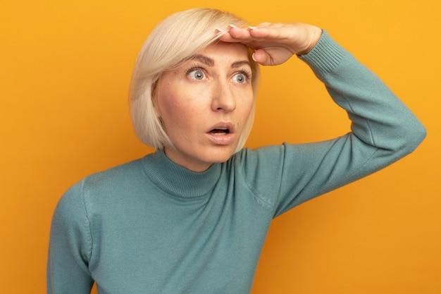 충격을받은 예쁜 금발의 슬라브 여자는 오렌지 벽에 고립 된 측면을보고 이마에 손바닥을 유지