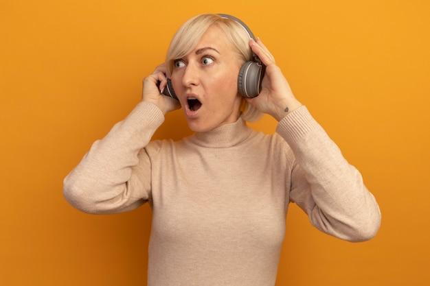 ヘッドフォンでショックを受けたかなり金髪のスラブ女性はオレンジ色の側面を見る
