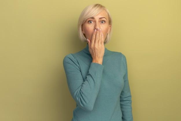 La donna slava abbastanza bionda scioccata mette la mano sulla bocca isolata sulla parete verde oliva