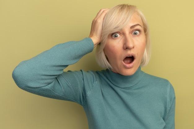 ショックを受けたかなり金髪のスラブ女性が頭に手を置き、オリーブグリーンのカメラを見る