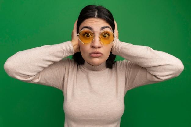 Ragazza caucasica abbastanza castana scioccata in occhiali da sole chiude le orecchie con le mani che guarda l'obbiettivo sul verde