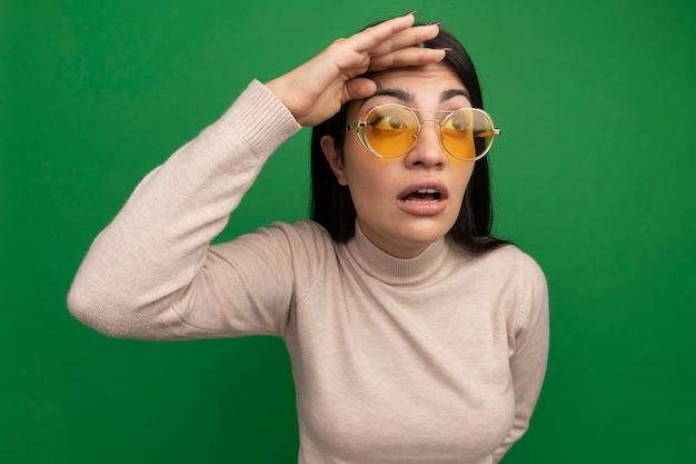 La ragazza caucasica abbastanza castana scioccata in occhiali da sole mantiene il palmo sulla fronte guardando il lato sul verde
