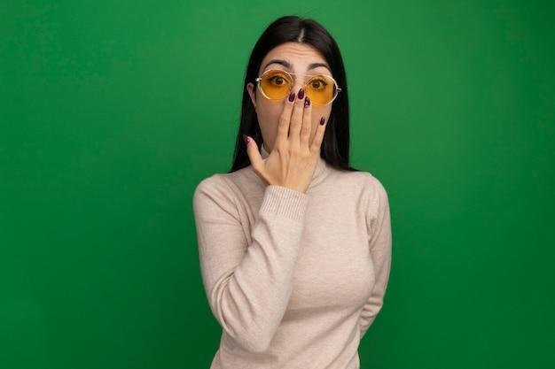 Ragazza caucasica abbastanza castana scioccata in occhiali da sole mette la mano sulla bocca sul verde