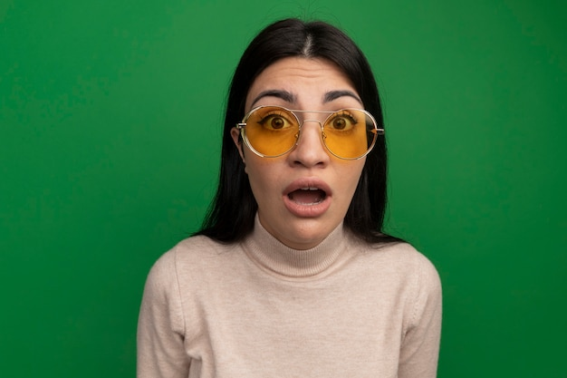 Шокированная симпатичная брюнетка в солнцезащитных очках смотрит на переднюю часть, изолированную на зеленой стене