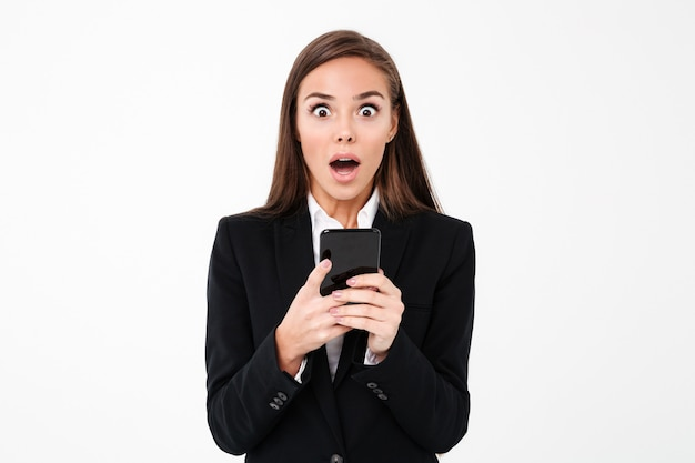 Shocked pretty businesswoman chatting by phone