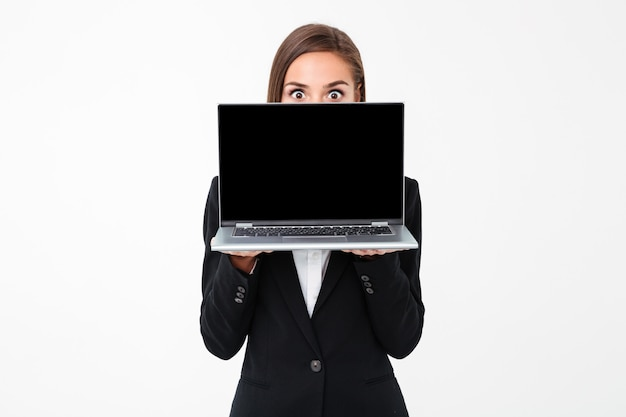 Shocked pretty businesswoman showing display of laptop computer