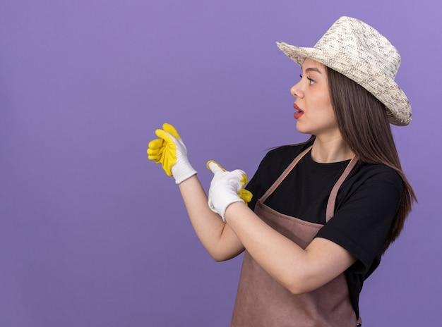 Шокированная красивая кавказская женщина-садовник в садовой шляпе и перчатках указывает назад, глядя в сторону