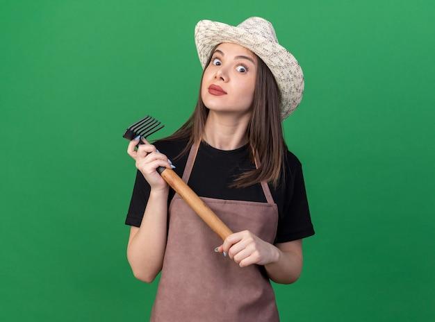복사 공간이 있는 녹색 벽에 격리된 갈퀴를 들고 정원용 모자를 쓰고 충격을 받은 백인 여성 정원사