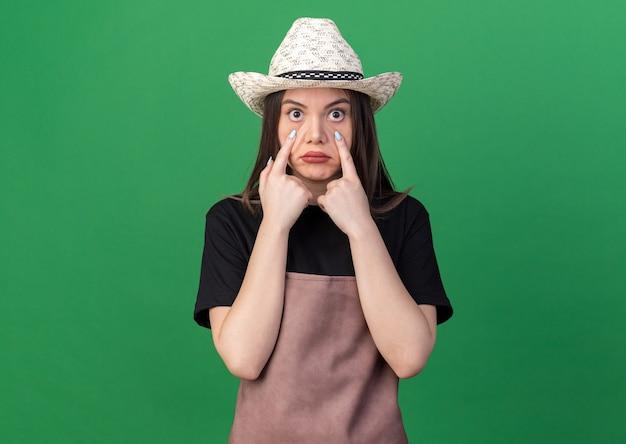ガーデニングの帽子をかぶってショックを受けたかなり白人女性の庭師は、コピースペースで緑の壁に分離されたまぶたを引っ張る