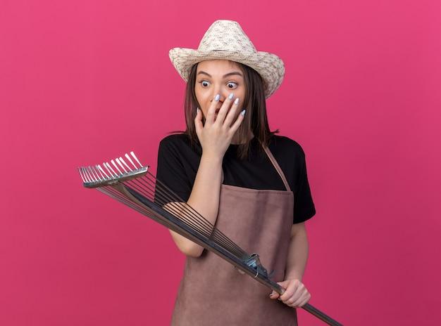 원예 모자를 쓰고 충격을받은 예쁜 백인 여성 정원사는 입을 잡고 복사 공간이 분홍색 벽에 고립 된 잎 갈퀴를보고 손을 넣습니다.