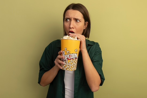 Shocked pretty caucasian woman eats and holds bucket of popcorn looking at side on olive green