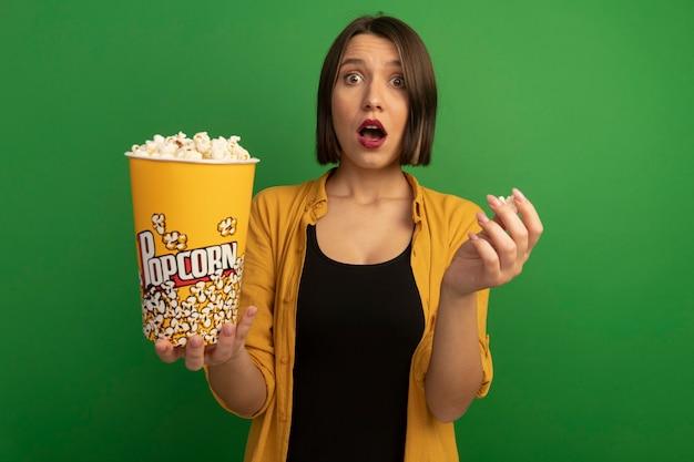 Shocked pretty caucasian woman holds bucket of popcorn on green