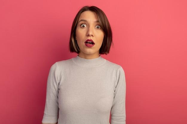 ショックを受けたかなり白人女性がピンクのカメラを見る